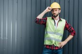 male engineer in safety vest and helmet standing near wall