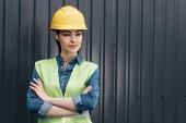 ženské inženýr v bezpečnostní vesta a přilba postavení s překřížením rukou na zeď