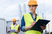 Fotografie professional female engineer in helmet writing in clipboard on roof, male colleague with blueprint behind