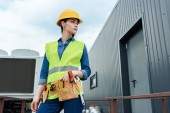 Photo female engineer with tool belt in safety vest and hardhat posing on construction