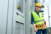 female architect with tool belt in safety vest and hardhat