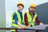 Fotografie profesionální technici v přilbách práci s plány a při pohledu na stavebnictví