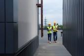 Fotografie architekti v přilbách s blueprint a kávy chůzi na střeše