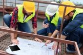 Fotografie tři inženýři v bezpečnostní vesty a Havířské práci s plány na střeše