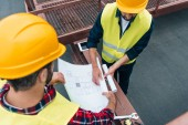 Fotografie overhead view of architects in safety vests and helmets working with blueprints