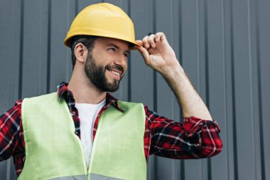 smiling male constructor in safety vest and helmet standing near wall