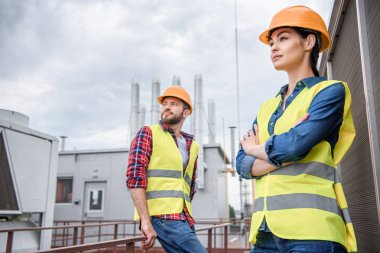 professional engineers in safety vests and helmets posing on roof