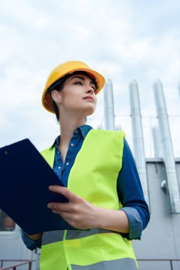 bottom view of beautiful female architect in safety vest and hardhat writing in clipboard