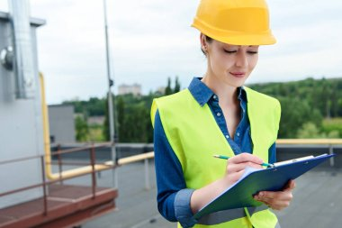 beautiful female engineer in safety vest and hardhat writing in clipboard