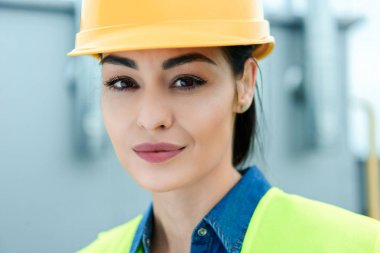 portrait of beautiful female architect in yellow hardhat