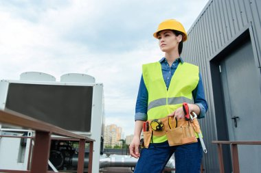 female engineer with tool belt posing in safety vest and hardhat