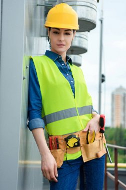 attractive engineer with tool belt in safety vest and hardhat
