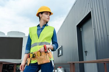 female engineer with tool belt in safety vest and hardhat posing on construction
