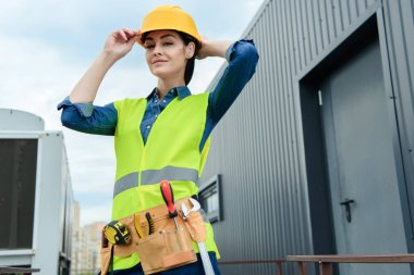 confident female architect with tool belt in safety vest and helmet