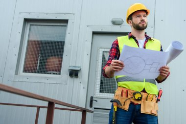 male professional engineer in safety vest and helmet working with blueprints