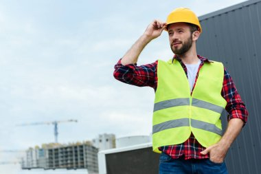 Professional confident engineer in safety vest and helmet posing on roof stock vector
