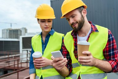 engineers in helmets using smartphone on coffee break on roof