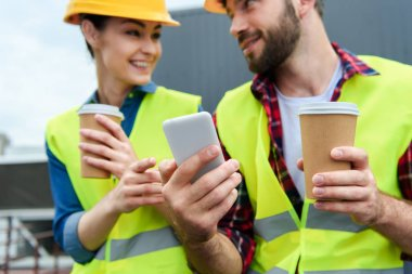 architects in safety vests and helmets using smartphone on coffee break