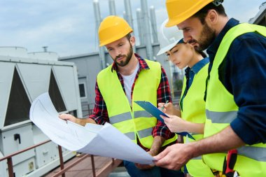 Professional engineers in safety vests and hardhats working with blueprints and clipboard on roof stock vector