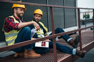 architects with blueprints and digital tablet with soundcloud website sitting on construction