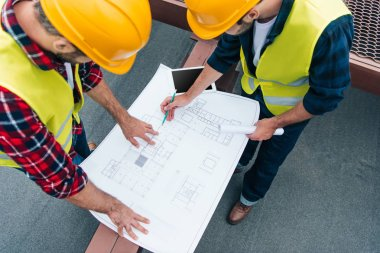 overhead view of architects in safety vests and helmets drawing on blueprints