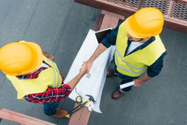 overhead view of engineers in helmets with blueprints shaking hands on roof