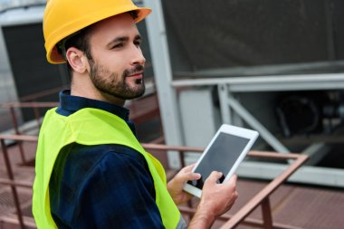 architect in safety vest and helmet using digital tablet with blank screen