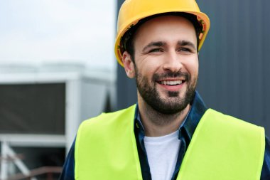 portrait of cheerful male engineer in safety vest and helmet
