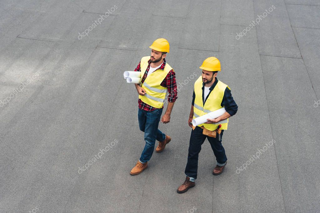 Overhead view of architects in safety vests and hardhats with blueprints stock vector