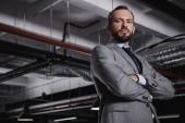 Fotografie Jistý podnikatel v šedém obleku pózuje s překřížením rukou