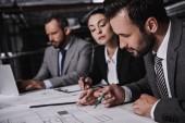 architekti a inženýři v oblecích spolupracovat s plány