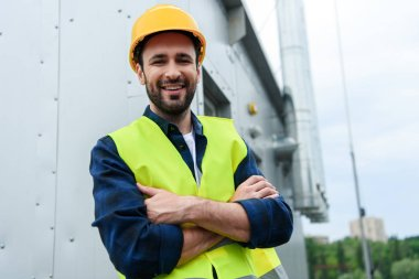 male smiling engineer in safety vest and helmet standing with crossed arms