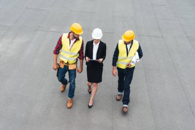 overhead view of female architect and male workers in helmets with clipboard and blueprints