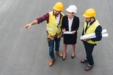 overhead view of female engineer and male workers with clipboard and blueprints pointing at construction