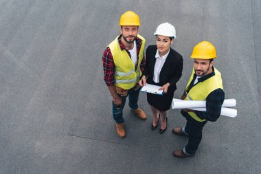 overhead view of female engineer and male workers with clipboard and blueprints