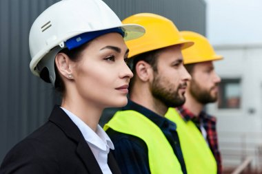 female engineer and male workers in helmets on construction