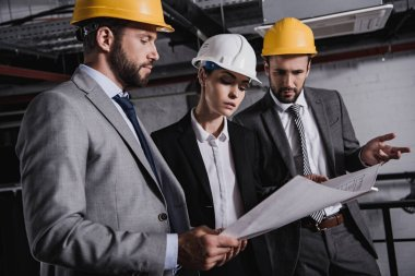 architects and engineers in suits and hardhats working with blueprint on construction