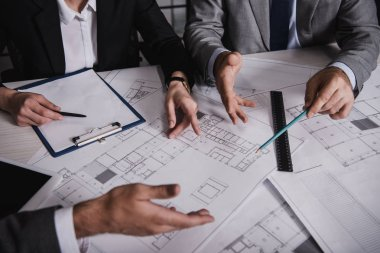 Cropped view of architects gesturing and working with blueprints stock vector