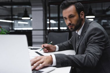 male engineer working with blueprints and laptop in office