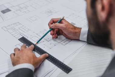 cropped view of architect working with blueprints, pencil and ruler