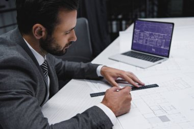 male engineer working with blueprints and laptop