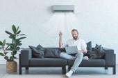 schöner Mann schaltet Klimaanlage mit Fernbedienung ein, während er Laptop auf dem heimischen Sofa benutzt