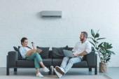 Paar schaltet Klimaanlage in der Sommerhitze ein, während es mit Buch und Laptop auf dem Sofa sitzt