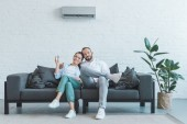 Fotografie couple turning on air conditioner during the summer heat at home