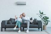 Fotografie zapnutí klimatizace v letních horkých doma pár