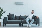 Fotografie Mann sitzt auf grauem Sofa mit Fernbedienung, Klimaanlage an der Wand