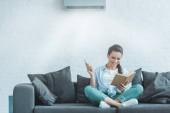 glückliche Frau liest Buch, während sie zu Hause Klimaanlage mit Fernbedienung einschaltet
