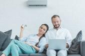 Ehepaar schaltet bei Sommerhitze Klimaanlage ein, während es Laptop benutzt