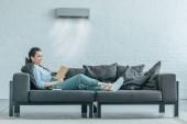 Fotografie žena čte knihu na gauči, klimatizace fouká na ní