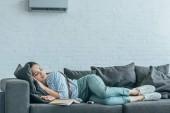Frau schläft auf Sofa mit Buch und Klimaanlage an der Wand